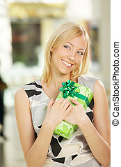 Pleasant gift - The smiling blonde presses to itself a gift...