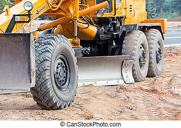 Closeup of road grader blade - Large yellow road grader...
