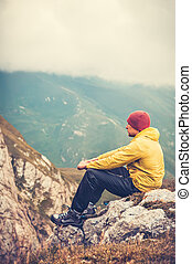 Man Traveler relaxing alone in Mountains Travel Lifestyle concept cloudy nature landscape on background