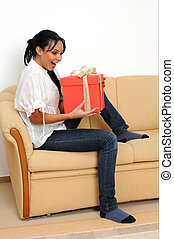 Young woman at home with a present.