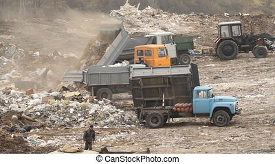 Garbage trucks unload garbage