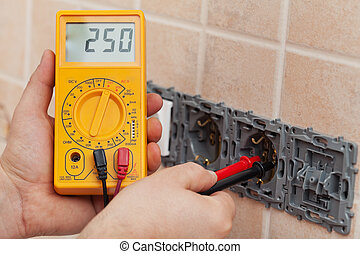 Electrician hands with multimeter measuring the voltage in a...