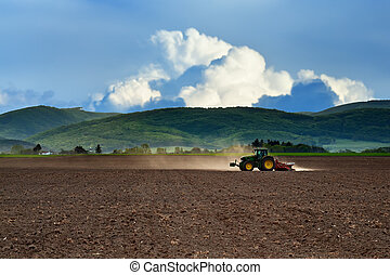 Tractor working on the field in late afternoon