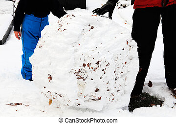 Snowball - Adult and child rolling a snowball to make a...