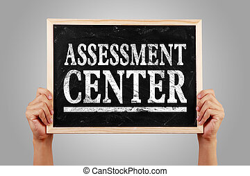 Assessment center - Hands are holding the blackboard of...