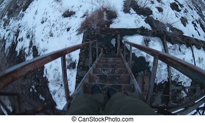 man walks down the stairs an old abandoned railway first-person