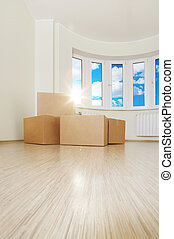 Moving - Heap of boxes in an empty living room against a...