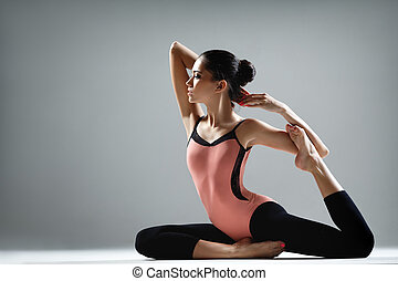 yoga exercise - young beautiful dancer posing on a studio...