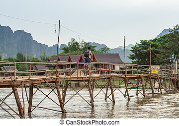 Wooden bridge over river song to riverside guesthouse, Vang...