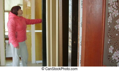 Customer chooses inner wooden door in doors store showroom