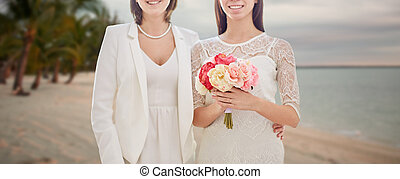 close up of happy lesbian couple with flowers - people,...