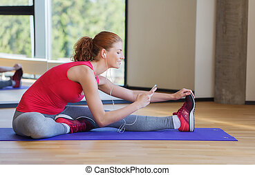 smiling woman stretching on mat in the gym - fitness, sport,...