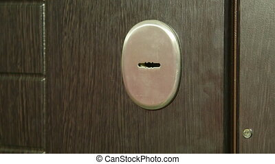 Female hand with key locking or unlocking the front door...