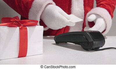 Santa Claus behind the counter using credit card reader -...