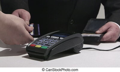Consumer using credit card processing terminal entering PIN...