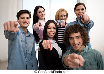 Business team smiling and pointing at camera