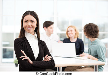 Businesswoman looking at camera with her business team on...