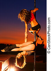 Young pole dance women - Two young pole dance women on urban...
