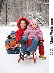 mother sits on sled with children in park at winter