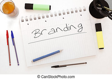 Branding - handwritten text in a notebook on a desk - 3d...