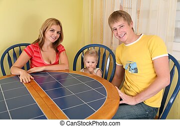parents with child sit at table in  room