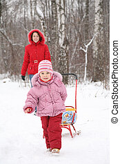 child with sled and mother in park at winter