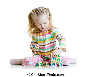 smiling little girl is building a toy block