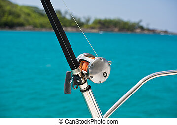 Fishing rod and reel on a boat. Horizontal shot