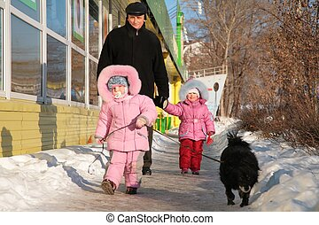 grandfather with child and dog walk on street in winter