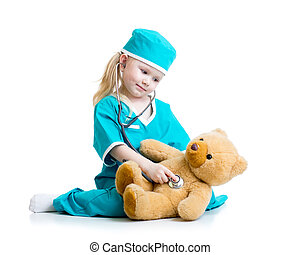 Adorable child with clothes of doctor examining bear toy -...