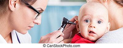 Pediatrician using otoscope to examine baby's ear