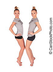 Twin sport girls stands on tiptoe face-to-face