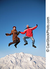 couple jump on top of snow hill