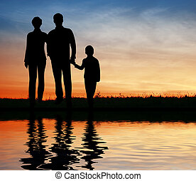 silhouette family on sunset coast