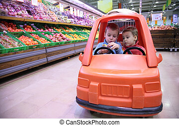 children in toy automobile in store