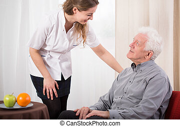 Nurse caring about elder man - Image of young nurse caring...