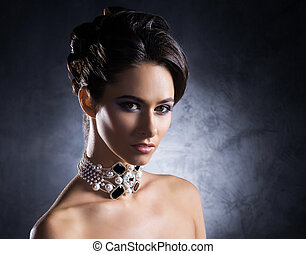 Young, beautiful and rich woman in jewels of platinum and...