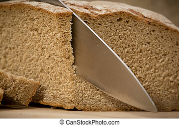 A slice of bread with butter on a chopping board.