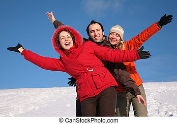 group of friends move by hands in winter on hillside