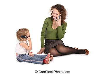 mother and daughter sitting they talk on the cell phones on...