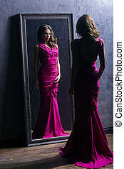 Young and gorgeous actress in a long dress preparing in a...