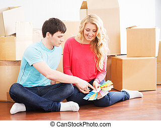 Young couple moving in a new home. Wife and husband...