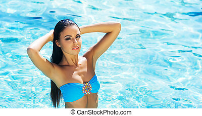 Beautiful, active and sporty girl swimming in a pool at...
