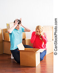 Young couple moving in a new home. Man and woman unboxing...