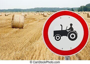 Tractor traffic sign in front of an agricultural field