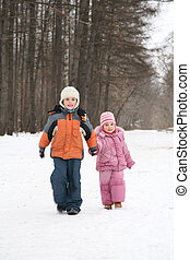 brother and sister walk in park in winter