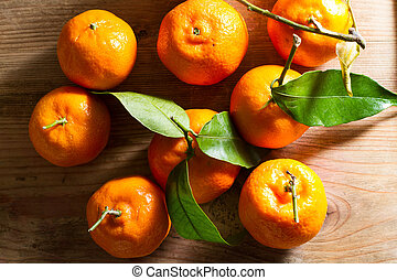 Clementines - Juicy, fresh clementines against a wooden...