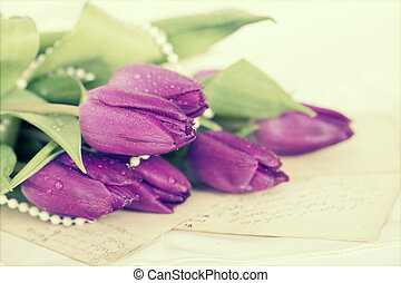 Old love letters and purple tulips. Retro style toned...