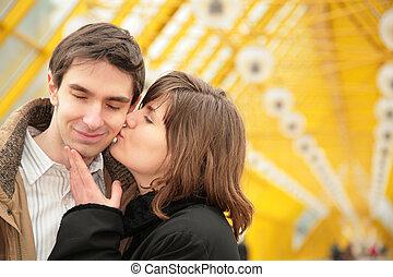 kissing couple on yellow bridge