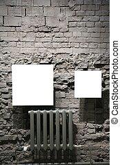 two blank frames on grey brick wall